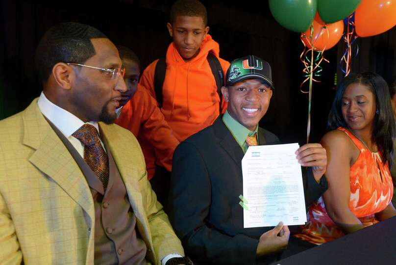 Ray Lewis III, second from right, shows his national letter-of-intent form as his father, former Bal
