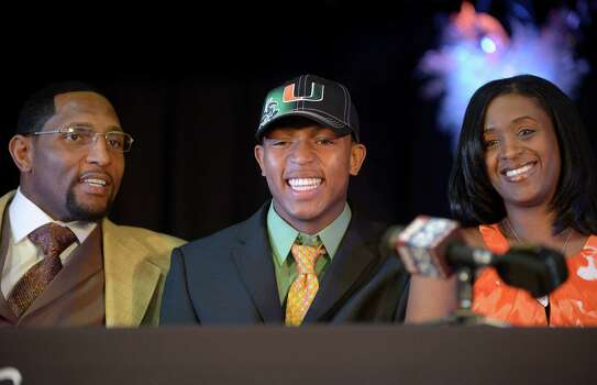 Ray Lewis III, center, poses for photos with his father, former Baltimore Ravens linebacker Ray Lewis Jr., left, and mother, Tatyana McCall, during a national signing day ceremony in the Lake Mary Prep auditorium in Lake Mary, Fla., Wednesday, Feb. 6, 2013. Lewis signed a letter of intent to play football at the University of Miami, where his father also played college football. (AP Photo/Phelan M. Ebenhack) Photo: Phelan M. Ebenhack, Associated Press / FR121174 AP