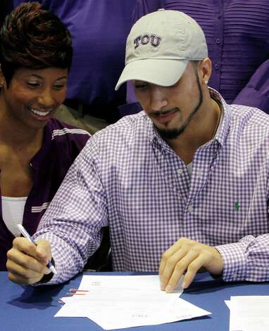 Nikki Luper watches her son, Cameron Echols-Luper, signs a letter of intent to attend TCU and play college football during National Signing Day on Wednesday, Feb. 6, 2013, in Auburn, Ala. (AP Photo/Butch Dill) Photo: Butch Dill, Associated Press / FR111446 AP