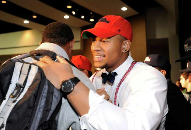 Grayson High School football player Robert Nkemdiche, the nation's top recruit, is congratulated by teammates after he announces his intent to play college football for Ole Miss, during a signing day ceremony at his high school auditorium in Grayson, Ga., Wednesday Feb. 6, 2013. (AP Photo/David Tulis) Photo: Dave Tulis, Associated Press / FR170493 AP