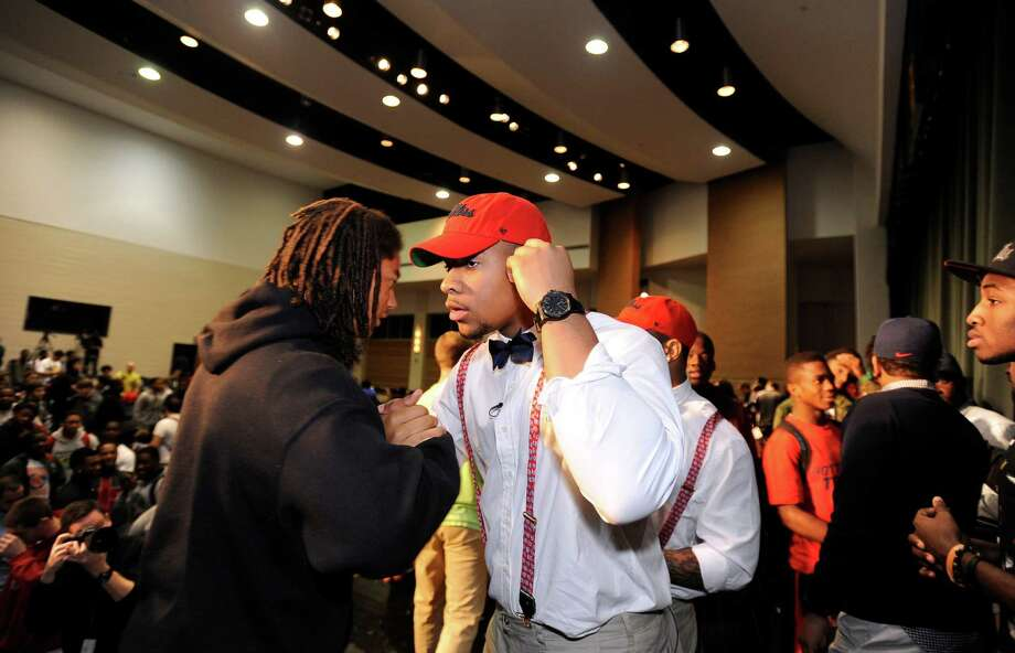 Grayson High School football player Robert Nkemdiche, the nation's top recruit, is congratulated by classmates after he announces his intent to play college football for Ole Miss, during a signing day ceremony at his high school auditorium in Grayson, Ga., Wednesday Feb. 6, 2013. (AP Photo/David Tulis) Photo: Dave Tulis, Associated Press / FR170493 AP