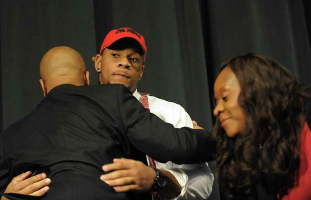 The nation's top recruit, Grayson High School's Robert Nkemdiche, center, hugs his father Sunday, left, and mother Beverly after announcing his intent to play college football for Ole Miss, during a signing day ceremony at his high school auditorium in Grayson, Ga., Wednesday Feb. 6, 2013. (AP Photo/David Tulis) Photo: Dave Tulis, Associated Press / FR170493 AP