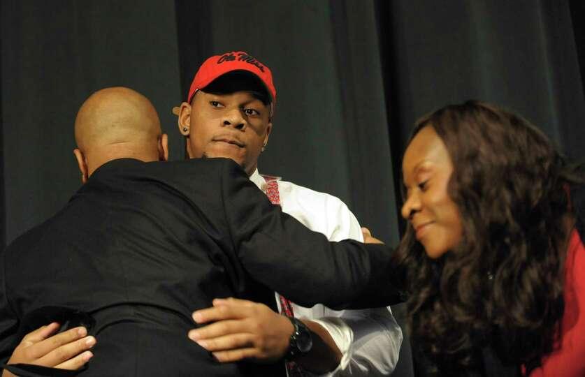 The nation's top recruit, Grayson High School's Robert Nkemdiche, center, hugs his father Sunday, le