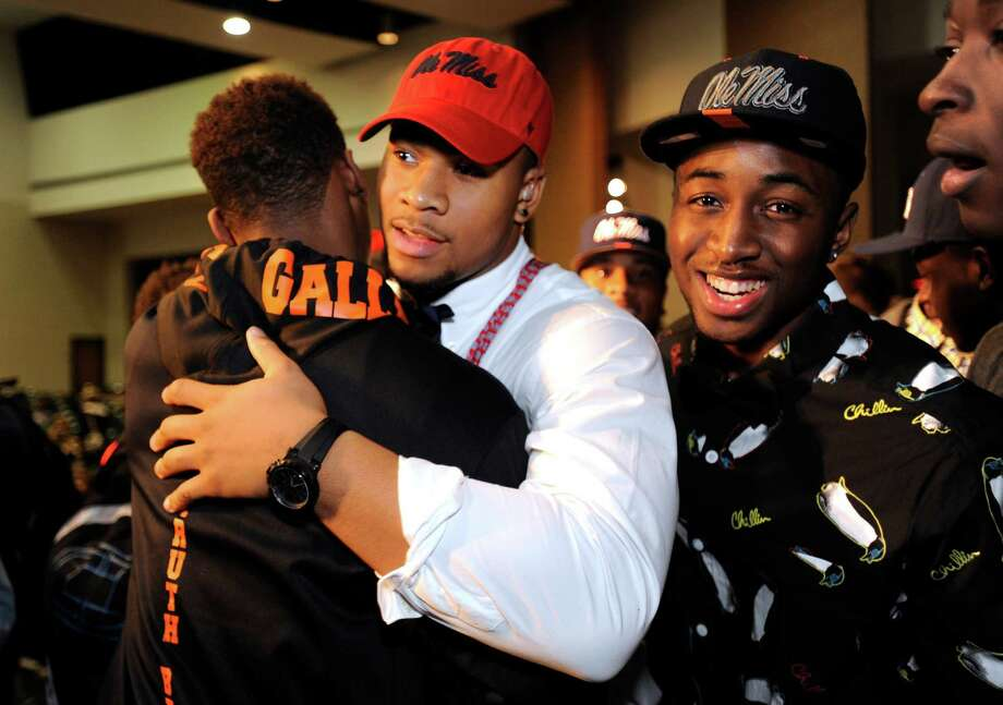 Grayson High School football player Robert Nkemdiche, center, the nation's top recruit, is congratulated by classmates after his announcement to play college football for Ole Miss, during a Grayson, Ga., signing ceremony Wednesday Feb. 6, 2013. (AP Photo/David Tulis) Photo: Dave Tulis, Associated Press / FR170493 AP