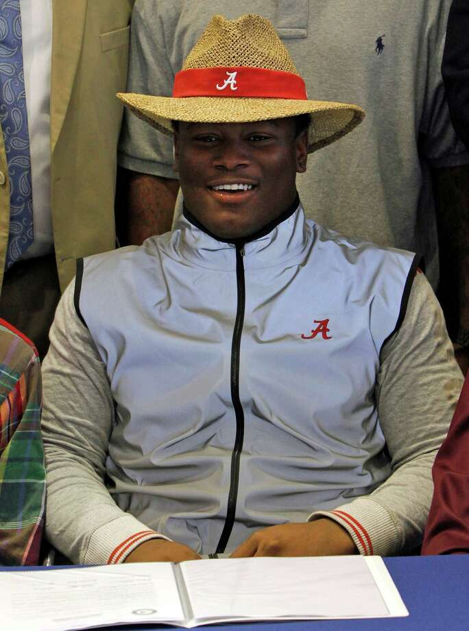 Reuben Foster dons an Alabama hat as he announces his intentions to attend the university and play college football during National Signing Day on Wednesday, Feb. 6, 2013, in Auburn, Ala. (AP Photo/Butch Dill) Photo: Butch Dill, Associated Press / FR111446 AP