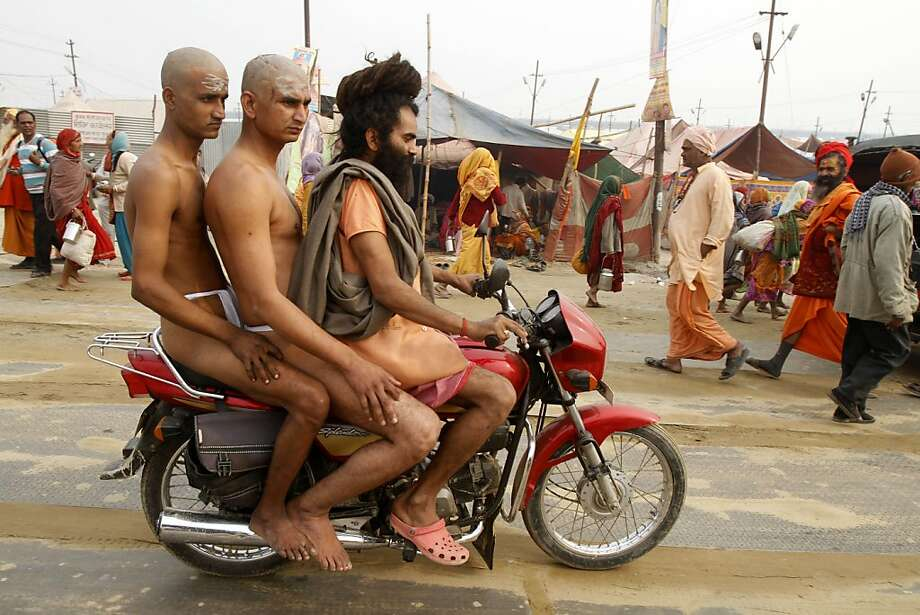 Born to ride naked:A naga sadhu (naked holy man) give two initiates a ride to the Maha Kumbh festival in Allahabad so they would not be late for rituals ridding themselves of all material ties. Naga sadhus renounce clothes and all other worldly possessions, with the possible exception of motorcycles. Photo: Rajesh Kumar Singh, Associated Press