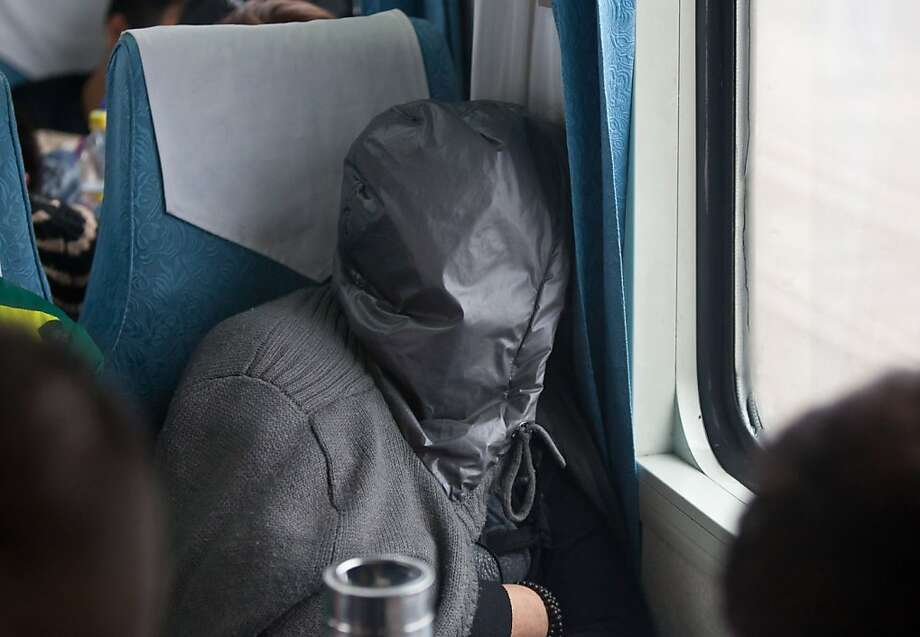 Don't breathe on me:A passenger riding the train from Guangzhou, China, to his hometown of Changchun is determined not to catch anything before the Lunar New Year festivities. Photo: Str, AFP/Getty Images
