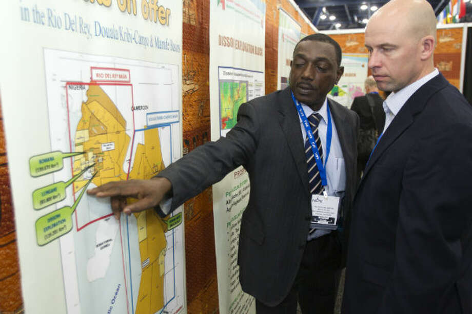 Jifon Francis, left, of the National Hydrocarbons Corporation of Camerooon, shows leasing blocks in Cameroon to Jonas Harrell, of Noble Energy, during the NAPE Expo at the George R. Brown Convention Center Tuesday, Feb. 5, 2013, in Houston.