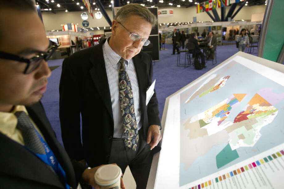 Ahmad Januri, left, of Petronas, looks at a map of exploration and production in Malaysia with David Smith, of Newfield Exploration Company during the NAPE Expo at the George R. Brown Convention Center Tuesday, Feb. 5, 2013, in Houston.