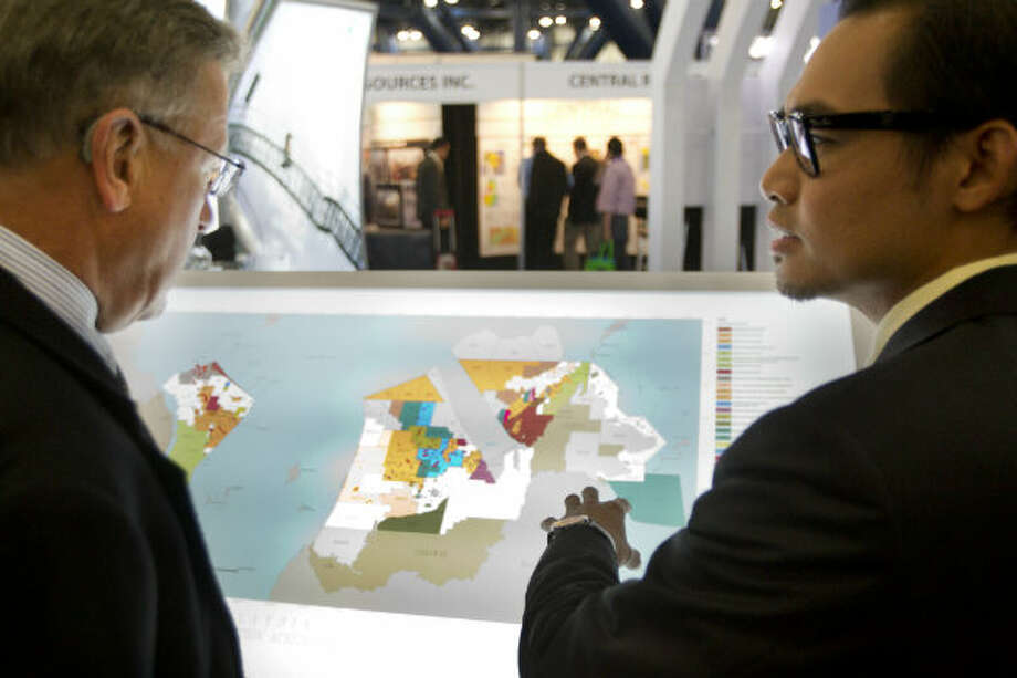 David Smith, of Newfield Exploration Company, left, looks at a map of exploration and production in Malaysia with Ahmad Januri, of Petronas, during the NAPE Expo at the George R. Brown Convention Center Tuesday, Feb. 5, 2013, in Houston.