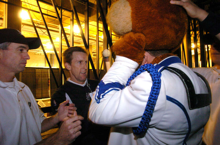 Former Spurs Coyote Tim Derk, second from left, assists the new man inside the suit with the mascot's head prior to the San Antonio Spurs and Sacramento Kings game on Nov. 4, 2004. Photo: BILLY CALZADA, SAN ANTONIO EXPRESS-NEWS / SAN ANTONIO EXPRESS-NEWS