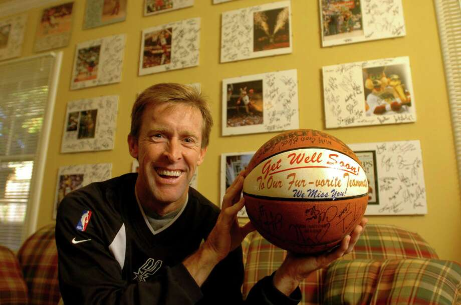 Tim Derk displays an autographed basketball given to him by the team. The wall is lined with photos of Derk as the Spurs Coyote, each photo signed by all the Spurs from each season that he was the team's mascot.  Photo: BILLY CALZADA, SAN ANTONIO EXPRESS-NEWS / SAN ANTONIO EXPRESS-NEWS