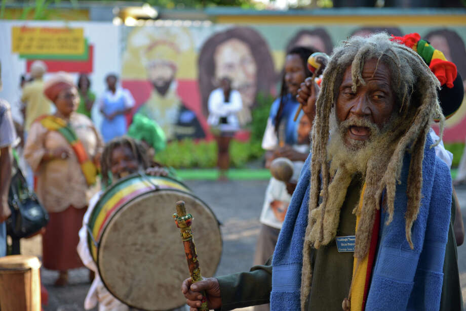 A Rastafarian priest leads a chant during the celebration of reggae music icon Bob Marley's 68th birthday in the yard of his Kingston home, in Jamaica, Wednesday, Feb. 6, 2013. Marley's relatives and old friends were joined by hundreds of tourists to dance and chant to the pounding of drums to honor the late reggae icon who died of cancer in 1981 at age 36. (AP Photo/ David McFadden) Photo: David McFadden
