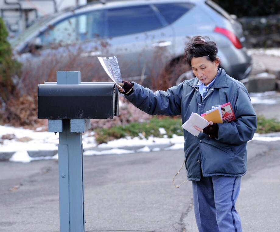 A U.S. Postal worker delivers mail on Henry Street in the Byram section of Greenwich, Wednesday, Feb. 6, 2013. The U.S. Postal Service says it plans to stop delivering mail on Saturdays. Photo: Bob Luckey / Greenwich Time