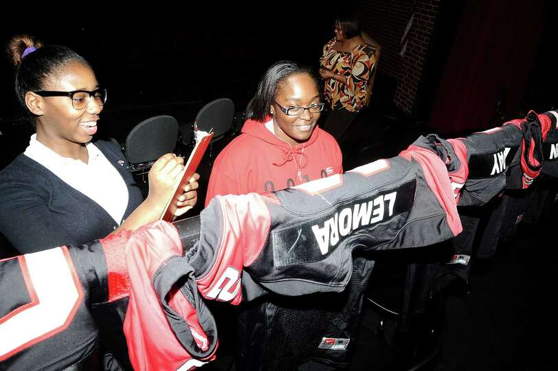 Donnicia Bill, right, and Toriell Atkins, left, help find places for the jerseys of the eleven stude
