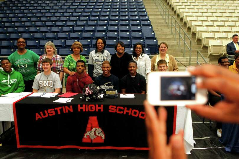 Austin High School students who committed to play football in college get their picture taken with t