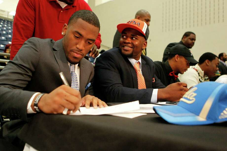 Fort Bend Marshall linebacker Deon Hollins Jr., left, signs during a mock commitment letter to play football at UCLA, next to  teammate Anthony Lee who committed to the University of Texas San Antonio during a signing day ceremony at the Buddy Hopson Field House Tuesday, Feb. 5, 2013, in Missouri City. Photo: Johnny Hanson, Houston Chronicle / © 2013  Houston Chronicle