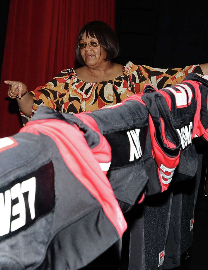 Memorial High School theater teacher Henrietta Haynes hold the railing and directs students to a place for the jerseys of the eleven students that will be signing contracts for Wednesdays Signing Day at Port Arthur Memorial High School on Tuesday, February 5, 2013. Photo taken: Randy Edwards/The Enterprise