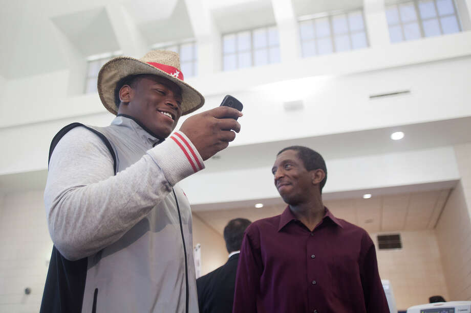 Reuben Foster sends a text message after announcing his intentions to attend the University of Alabama and play college football during National Signing Day on Wednesday, Feb. 6, 2013, in Auburn, Ala.  (AP Photo/Opelika-Auburn News, Albert Cesare) Photo: Albert Cesare, Associated Press / Opelika-Auburn News