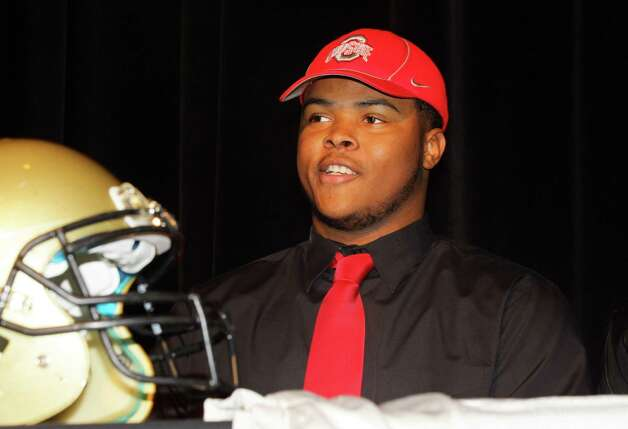Michael Hill, a senior at Pendleton High School, dons an Ohio State cap after signing a  letter of Intent on Wednesday, Feb. 6, 2013,  to attend the university and play college football during a signing day news press conference in Pendleton, S.C. (AP Photo/The Independent-Mail, Ken Ruinard) THE GREENVILLE NEWS OUT, SENECA NEWS OUT Photo: Ken Ruinard, Associated Press / The Independent-Mail