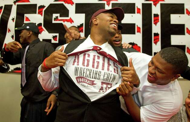 Texas A&M signee Hardreck Walker and his brother Chris Hall, right, laugh as Hardreck shows off an Aggies t-shirt during a national signing ceremony at Westfield High School Wednesday, Feb. 6, 2013, in Houston.(AP Photo/Houston Chronicle,  Brett Coomer) MANDATORY CREDIT \ Photo: Brett Coomer, Associated Press / Houston Chronicle