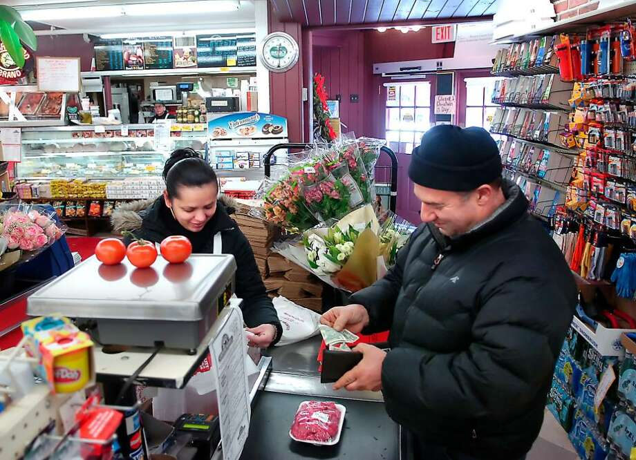 Cashier, Belkis Zepeda, left, rings up customer, Joe Delia of Stamford right, who is buying  tomatos and chop meat at Giovanni's Country Market, Stamford. Photo: Bob Luckey / Stamford Advocate