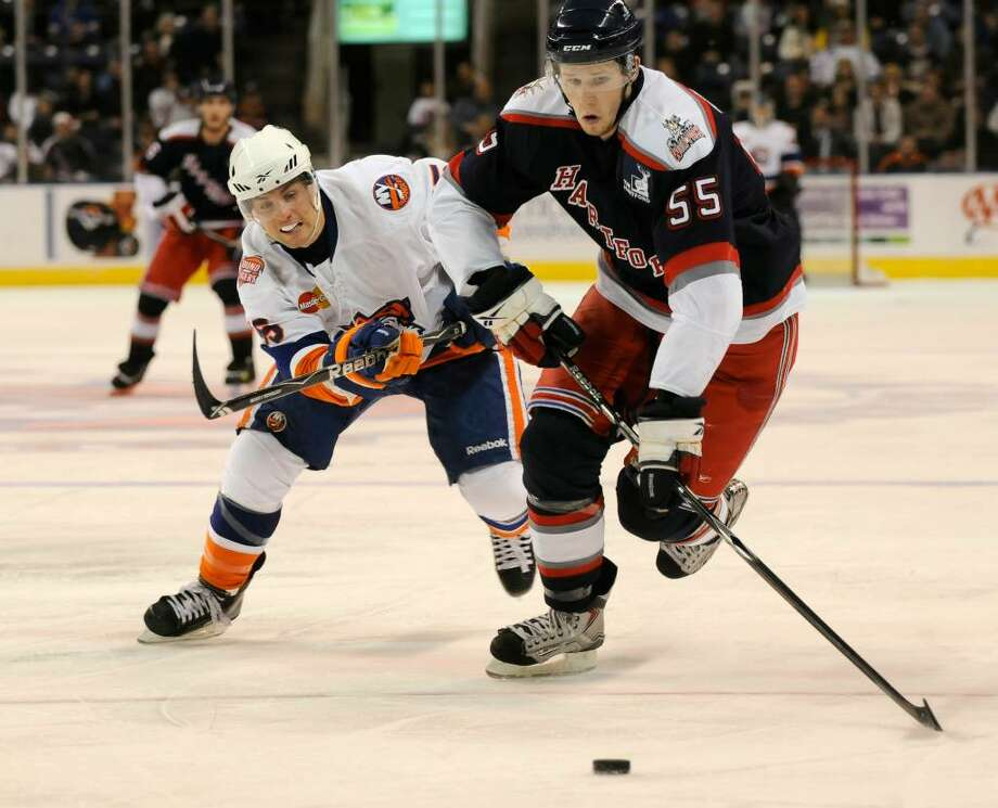 "Bridgeport Sound Tigers host the Hartford Wolf Pack at the Arena at Harbor Yard in Bridgeport, CT on Saturday, Dec. 26, 2009. Sound Tiger #55 Pascal Morency vies for the puck with Wolf Pack #55 Nigel Williams./ Shelley Cryan for the CT Post Photo: Shelley Cryan / 2009 Michelle ""Shelley"" Cryan"