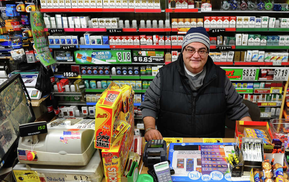 "Owner of Nick's Grocery store, Osama ""Sammy"" Ghalayini poses inside the shop in Bridgeport, Conn. on Wednesday February 3, 2013. Two masked gumen tried to rob him yesterday evening but he used his gun to defend himself. A gun battle ensued leaving many spots in the store riddled with bullet holes. You can see damage on the security screen at the left where a bullet hit the edge of it. Photo: Christian Abraham / Connecticut Post"