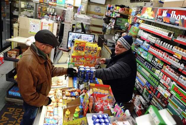 "Owner of Nick's Grocery store, Osama ""Sammy"" Ghalayini, right, serves customer Mike Sull at the shop in Bridgeport, Conn. on Wednesday February 3, 2013. Two masked gumen tried to rob him yesterday evening but he used his gun to defend himself. A gun battle ensued leaving many spots in the store riddled with bullet holes. Sull said, ""I was shook when I heard the news."" Sull has been coming to this market regularly since 1978. Photo: Christian Abraham / Connecticut Post"