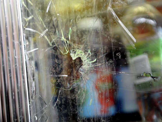 "Tape holds up glass in a refrigerator that was hit with a bullet at Nick's Grocery store in Bridgeport, Conn. on Wednesday February 3, 2013. Two masked gumen tried to rob owner Osama ""Sammy"" Ghalayini yesterday evening but he used his gun to defend himself. A gun battle ensued leaving many spots in the store riddled with bullet holes. Photo: Christian Abraham / Connecticut Post"