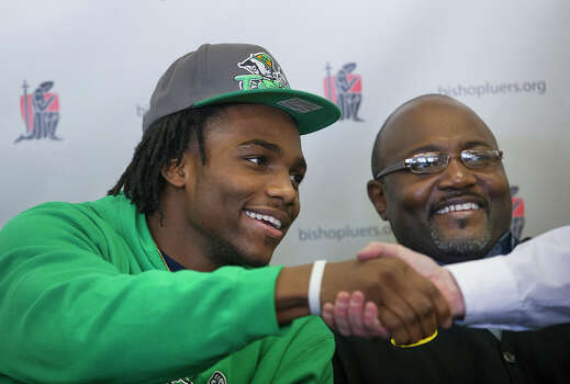 Jaylon Smith, a linebacker from Bishop Luers, greets someone while sitting next to his father, Roger Smith, Wednesday, Feb. 6, 2013, in Fort Wayne, Ind. Smith signed a letter of intent with Notre Dame. (AP Photo/The Journal-Gazette, Swikar Patel) NEWS-SENTINEL OUT  MAGS OUT  NO SALES Photo: Swikar Patel, Associated Press / The Journal-Gazette