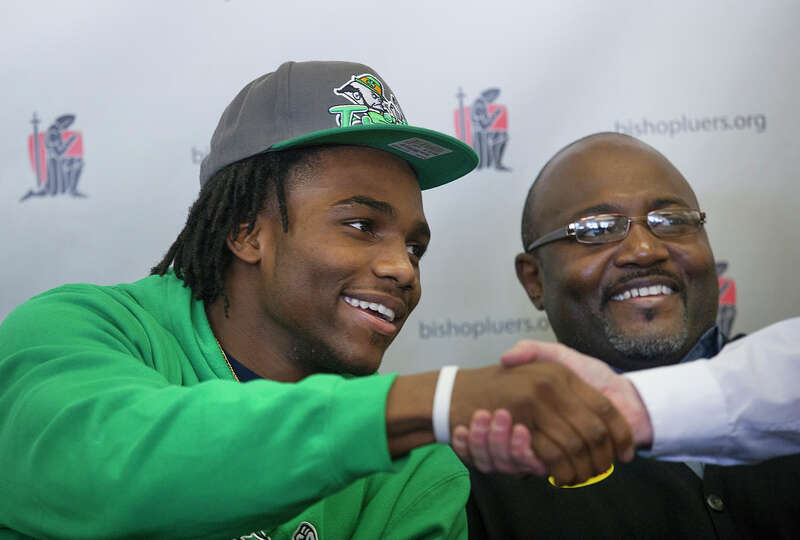 Jaylon Smith, a linebacker from Bishop Luers, greets someone while sitting next to his father, Roger