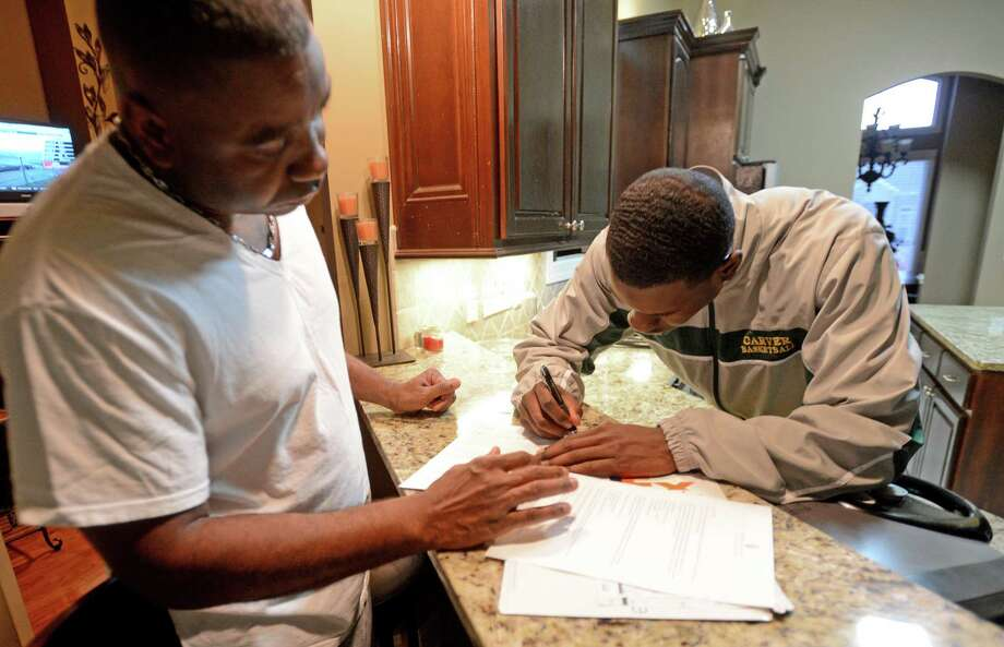 Ojedita Johnson, left, looks on as his son Carver High School quarterback Jeremy Johnson signs his letter of intent to attend Auburn University during a national signing day at their home Wednesday, Feb. 6, 2013, in Montgomery, Ala.  (AP Photo/AL.com, Julie Bennett) MAGS OUT Photo: JULIE BENNETT, Associated Press / AL.COM