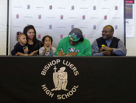 Jaylon Smith, second from right, signs a letter of intent with Notre Dame, while seated with his father, Roger Smith, right; mother, Sophia Woodson, second from left; cousin Alaja Williams, 2, left; and brother Leslie Woodson, 3, at Bishop Luers High School on Wednesday, Feb. 6, 2013, in Fort Wayne, Ind. (AP Photo/The Journal-Gazette, Swikar Patel) NEWS-SENTINEL OUT  MAGS OUT  NO SALES Photo: Swikar Patel, Associated Press / The Journal-Gazette