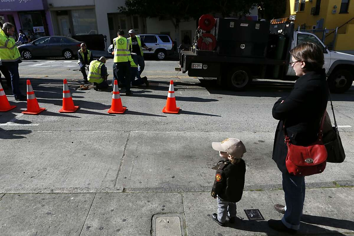 Wearing his custom junior Muni operator jacket, Reed Bell (2) and his mother Susan, of San Francisco, watch as San Francisco Municipal Transit Authority personnel repair a portion of a track where an incident involving a cable car resulted in seven injuries near the intersection of Powell and Washington Streets on Wednesday, February 6, 2013 in San Francisco, Calif.