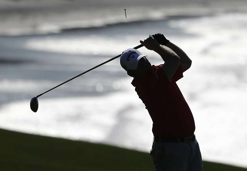J.B. Holmes follows his drive from the 14th tee of the Pebble Beach Golf Links during a practice rou