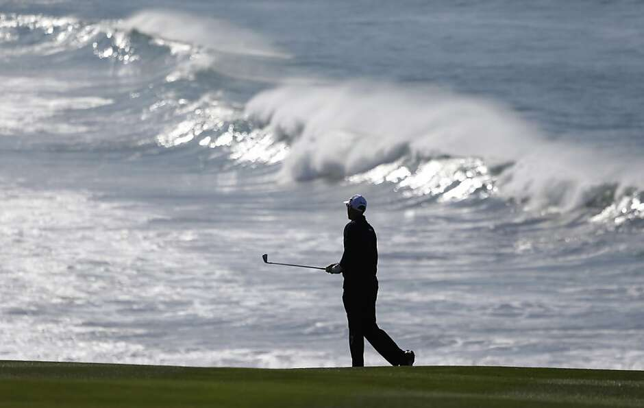 Cameron Percy of Australia follows his shot from the fairway to the ninth green of the Pebble Beach