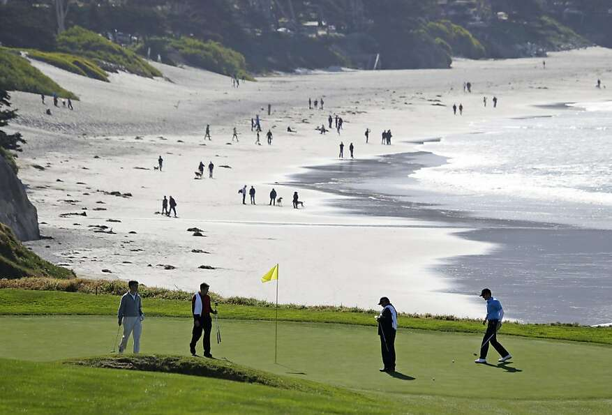 Roberto Castro, right, walks to his ball on the tenth green of the Pebble Beach Golf Links during a