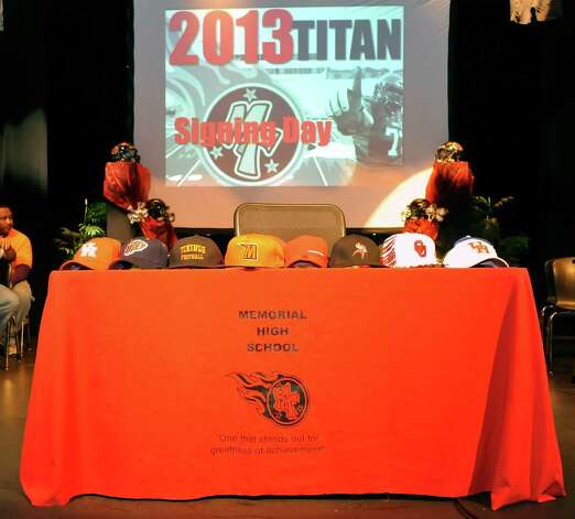 The hats sat waiting for each individual football player to claim his when he came to this table to sign his letter of intent.  The Port Arthur Memorial football team held their signing ceremony in its auditorium Wednesday morning. Twelve football players signed with colleges. Wednesday is National Signing Day, which is the first day high school football players can sign with colleges. Memorial had 11 players sign with colleges in 2012, and the school's football program is regularly turning out college players. Dave Ryan/The Enterprise Photo: Dave Ryan