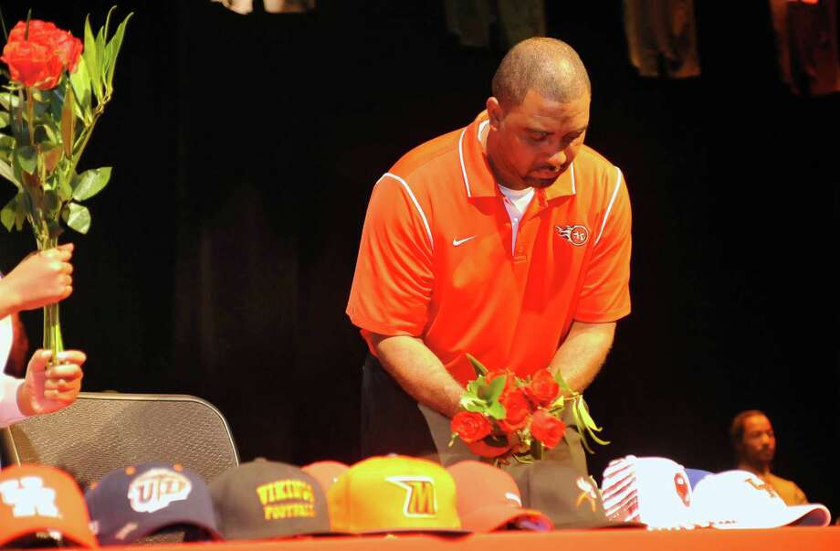 Head football coach Kenny Harrison re-arranges the flowers on the signing table they players traditionally give to their mothers. The Port Arthur Memorial football team held their signing ceremony in its auditorium Wednesday morning. Twelve football players signed with colleges. Wednesday is National Signing Day, which is the first day high school football players can sign with colleges. Memorial had 11 players sign with colleges in 2012, and the school's football program is regularly turning out college players. Dave Ryan/The Enterprise Photo: Dave Ryan