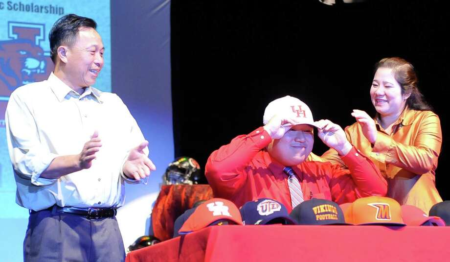 With his family behing him, Pt. Arthur Memorial Senior Toan Nguyen, center, puts on his University of Houston hat.  Nguyen is going there on an academic scholarship. The Port Arthur Memorial football team held their signing ceremony in its auditorium Wednesday morning. Twelve football players signed with colleges. Wednesday is National Signing Day, which is the first day high school football players can sign with colleges. Memorial had 11 players sign with colleges in 2012, and the school's football program is regularly turning out college players. Dave Ryan/The Enterprise Photo: Dave Ryan