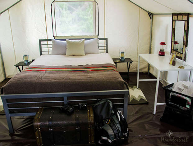"The ""Glamping"" tent is furnished with a Queen-size bed, hat and coat rack, towel rack, console table with mirror, indoor/outdoor table with two chairs, a trunk, plastic tote baskets and waffle-weave towels. Photo: Wanderlust Hospitality"
