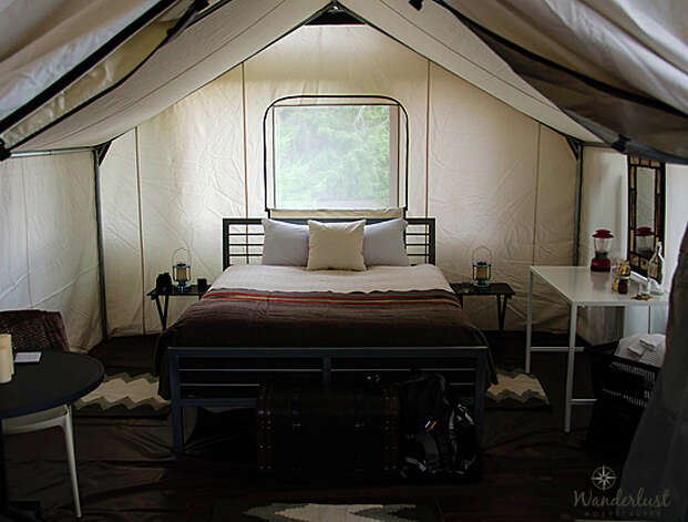 "The ""Glamping"" tent is 12 feet by 14 feet, five feet tall at the side walls and 8 feet, six inches tall at the peak, with three screen windows, a ""sweeping tent entry with screen and canvas portions"" and a vinyl floor with throw rugs. Photo: Wanderlust Hospitality"
