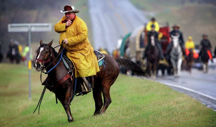 Arlis Young, Trail Boss of South Texas Trail Ride, talks in his radio to a scout rider, in the driving rain along U.S. Highway 181.  The ride started in Falls City, today, Wednesday, Feb. 6, 2013, and continued to Floresville. Photo: Bob Owen, San Antonio Express-News / © 2012 San Antonio Express-News