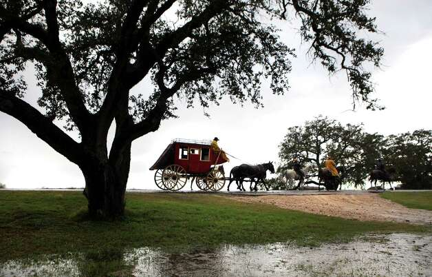 A stagecoach in the South Texas Trail Ride ambles north of US. Highway 181 in a driving rain.  The segment of the ride started in Falls City today, Wednesday, Feb. 6, 2013, and reached Floresville. Photo: Bob Owen, San Antonio Express-News / © 2012 San Antonio Express-News