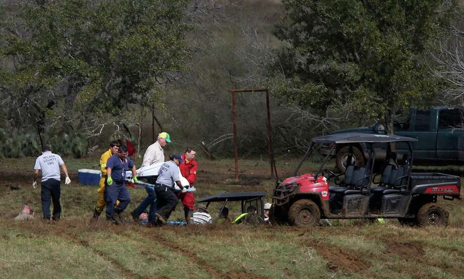 Officials carry a body from the ranch stock tank where the Chevrolet Tahoe ended up crashing after being pursued by a Wilson County deputy. Photo: Lisa Krantz, San Antonio Express-News / © 2012 San Antonio Express-News