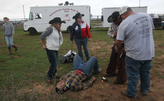 Chris Garcia,17, (on the ground) waits for an ambulance after he got bucked off a horse before the International Laredo Trail Riders Association rolled out of the Devine area Wednesday February 6, 2013. The ride is also known as the Laredo Trail Ride and will arrive in San Antonio Friday for the San Antonio Stock Show & Rodeo. Photo: JOHN DAVENPORT, San Antonio Express-News / ©San Antonio Express-News/Photo Can Be Sold to the Public