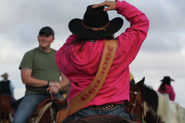 Laredo Trail Ride queen Mariah Seaman,16, adjusts her hat Wednesday February 6, 2013 before getting back on the trail after a break near Devine, Texas. The riders will arrive in San Antonio February 8. Photo: JOHN DAVENPORT, San Antonio Express-News / ©San Antonio Express-News/Photo Can Be Sold to the Public