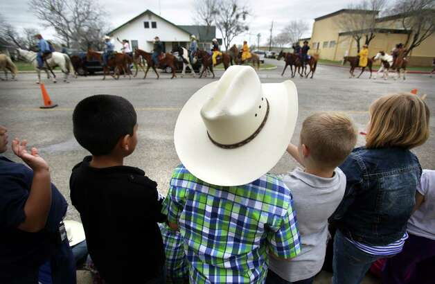 Students from Poth Elementary School line the sidewalk to wave at members of the South Texas Trail Ride as they ride by.  The segment of the ride started in Falls City today, Wednesday, Feb. 6, 2013, and reached Floresville. Photo: Bob Owen, San Antonio Express-News / © 2012 San Antonio Express-News