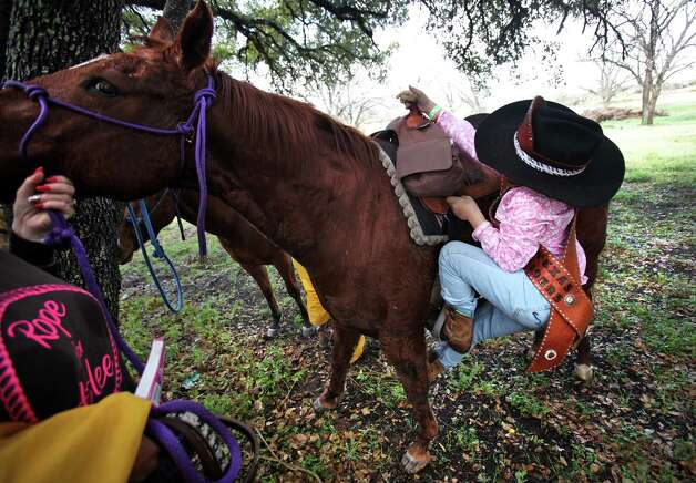 Abigail Atkinson, Mascot for the South Texas Trail Ride, struggles to mount a horse after the group stopped for lunch at the VFW Post 8555 in Poth, TX.  The segment of the ride started in Falls City today, Wednesday, Feb. 6, 2013, and reached Floresville. Photo: Bob Owen, San Antonio Express-News / © 2012 San Antonio Express-News